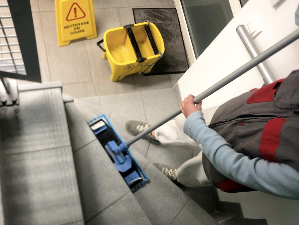 photo d'un escalier où une personne entretien le sol d'une copropriété ou d'un immeuble