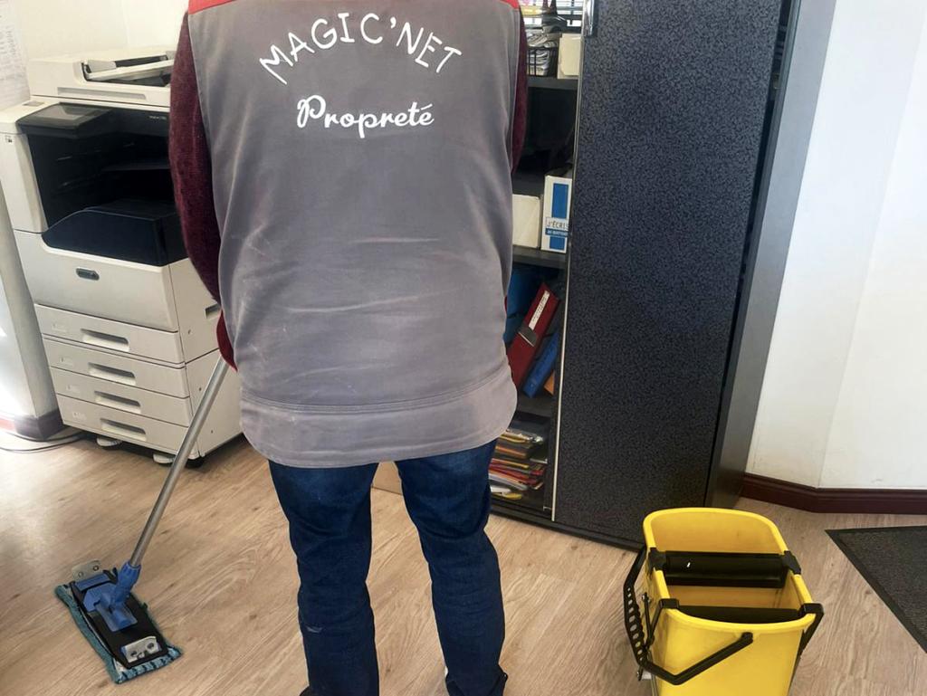nettoyage d'un espace de travail une personne avec une serpiere nettoie un parquet